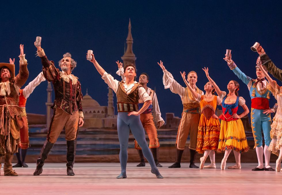 Francisco Estevez, in blue tights and a brown vest, holds a silver cup over his head along with the rest of the cast of Colorado Ballet's Don Quixote.