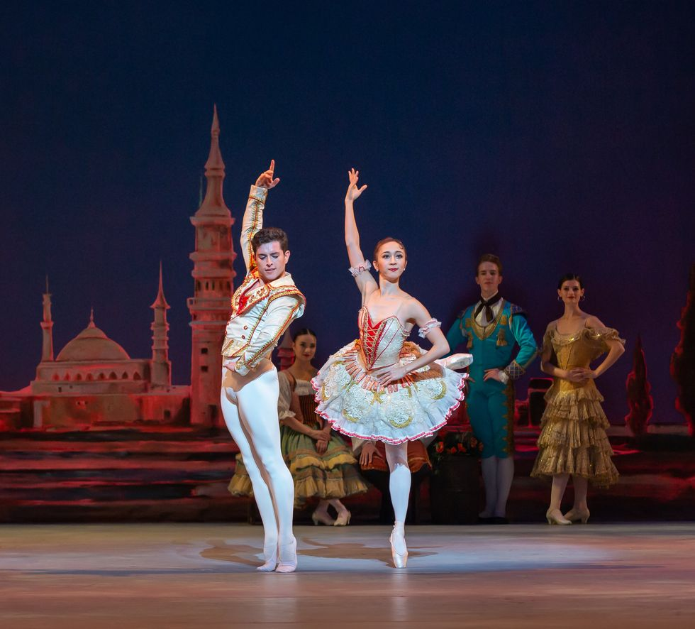 Francisco Estevez and his partner Asuka Sasaki wear white, gold and red Spanish-style costumes. Estevez stands in 6th position on demit pointe while Sasaki balances in attitude derriere.
