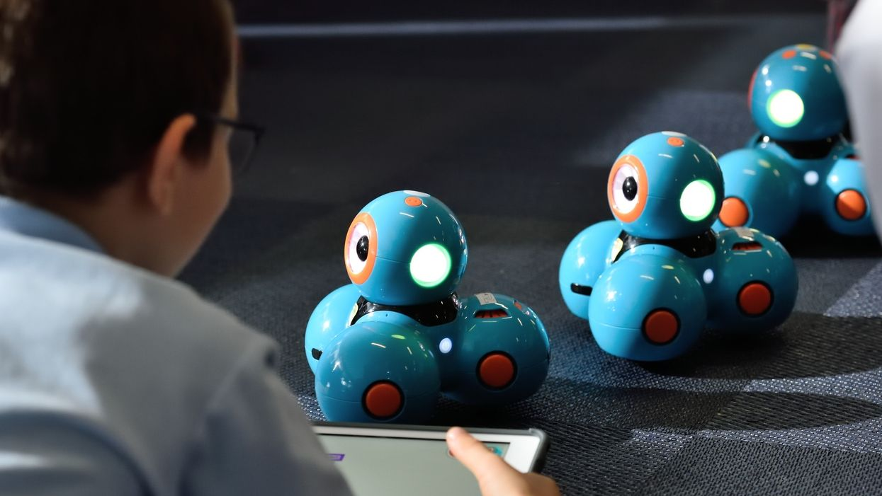 Children playing with tablet and smart robot toys.
