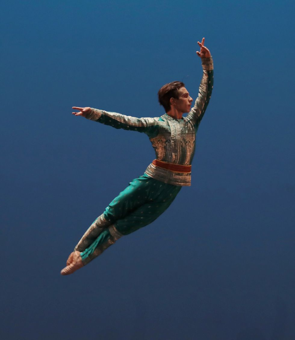 Francesco Mura jumps into the air with his legs pressed togetherin fifth position. His costume includes green and gold tunic and pants.