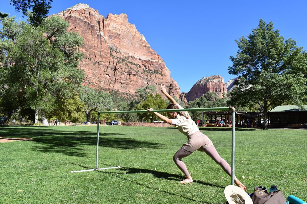 Longoria in a cambr\u00e9 forward as she pli\u00e9s on her supporting leg and her working leg extends in a tendu derriere. She is at the ballet barre on the lawn in front of a vast mountain view.
