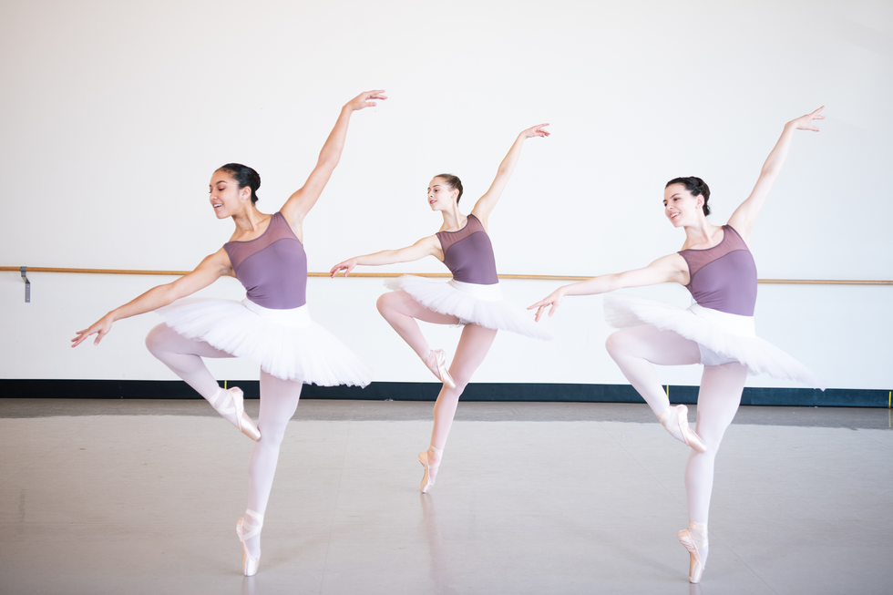 Three teen girls in purple leotards and white practice tutus are in passe en pointe. They lean slightly away from their working leg, reaching towards the floor with one arm with the other arm up.