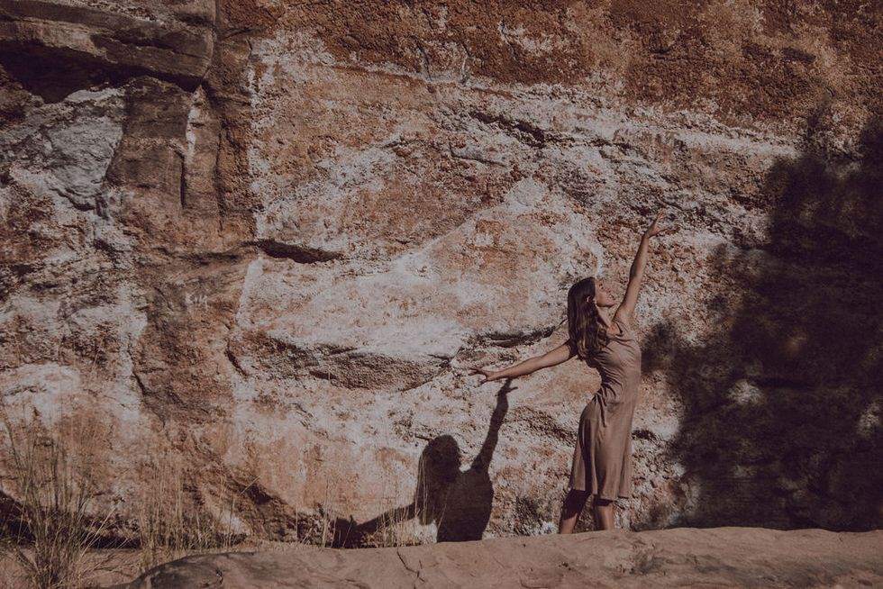 Longoria, with long brown hair and a tan dress, blends in with her rocky background, dancing with arms raised.
