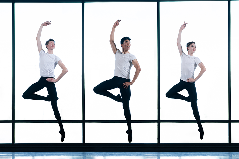 Three teen boys in black tights and white shirts jump in front of large windows in a studio. They have one leg in passe, one arm in fifth position and the other hand on their hips