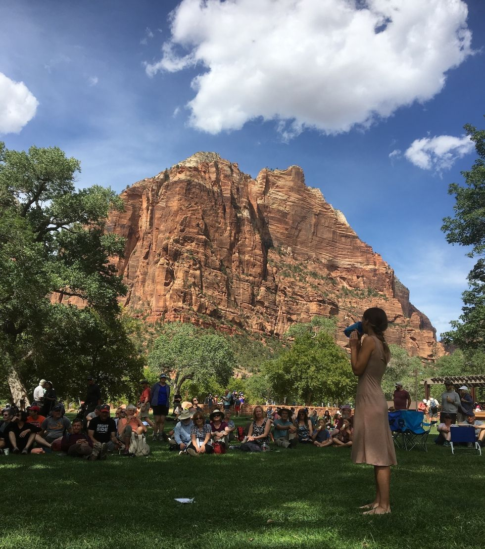Longoria sips from a water bottle will standing on a grassy lawn. A large group of park visitors are seated in the grass watching.