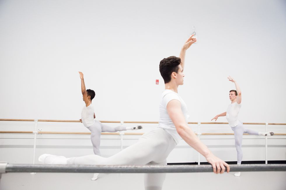 A group of young men taking class. They wear grey tights and white shirts. They are in an attitude at the barre.