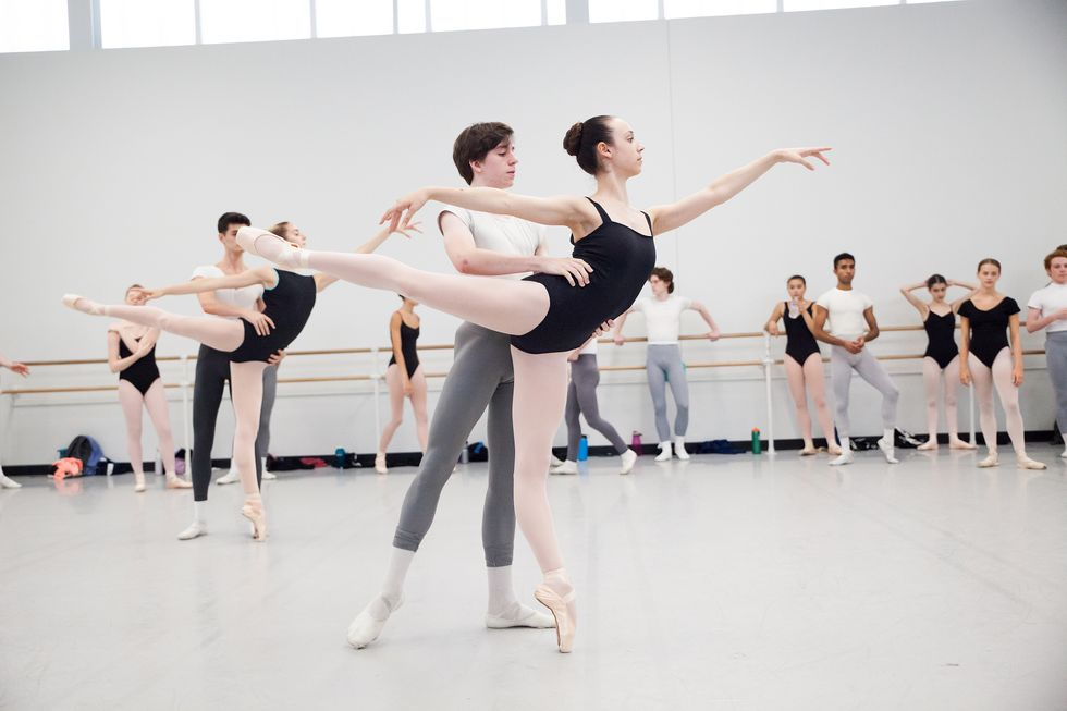 A partnering class, with two couples in the center of the studio and the rest of the students watching in the back. The young men support the young women in a first arabesque.