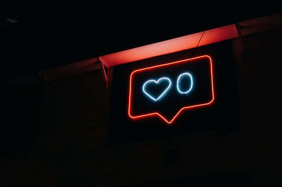 Neon sign of an Instagram like notification with a 0 next to the heart