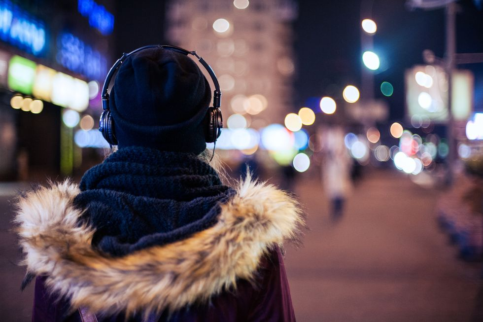 A woman wearing a winter coat, hat and scarf and headphones walks through a city street at night. We only see her from the back.