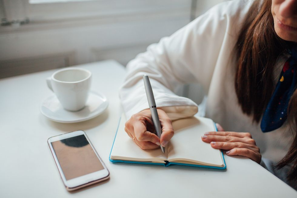 A woman writes in a blue journal on a white table. She wears a white top and has an iPhone and white mug next to her.