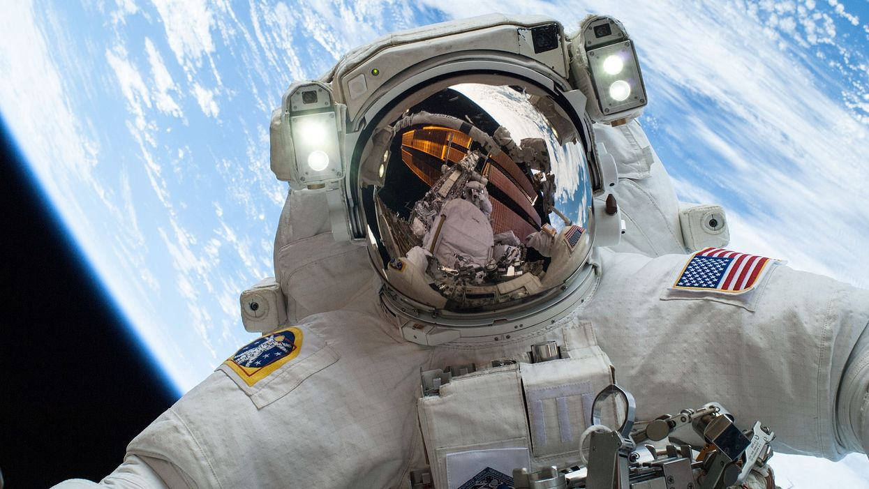 NASA astronaut taking a selfie in space with Earth in the background