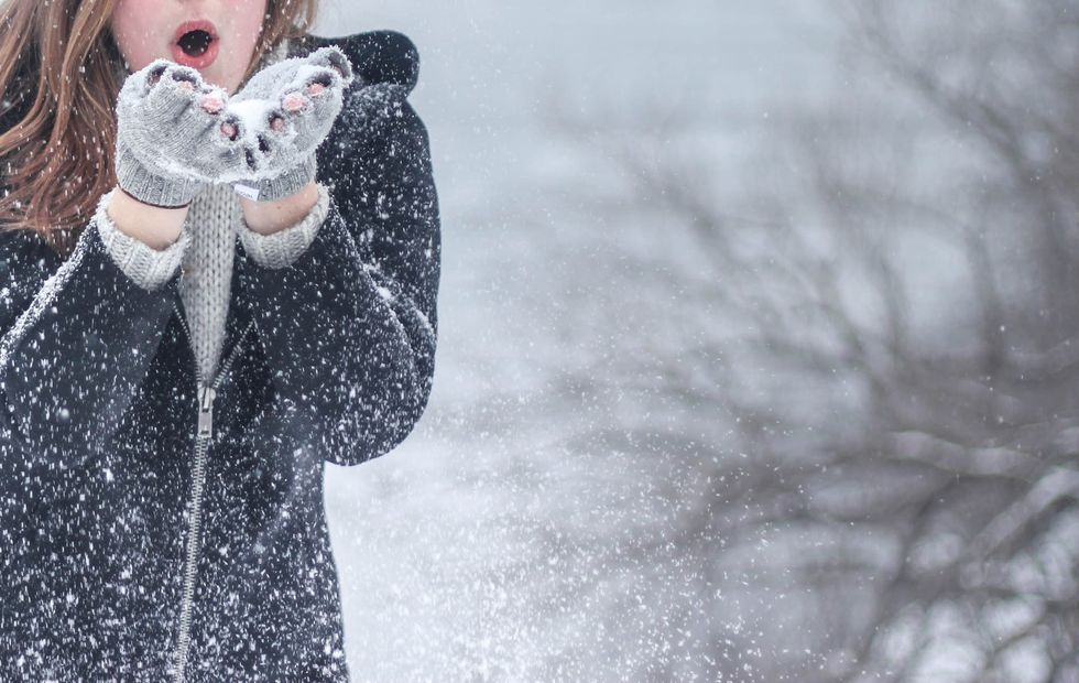 Woman in a winter gear blowing snow from the palm of her hands with her eyes closed.