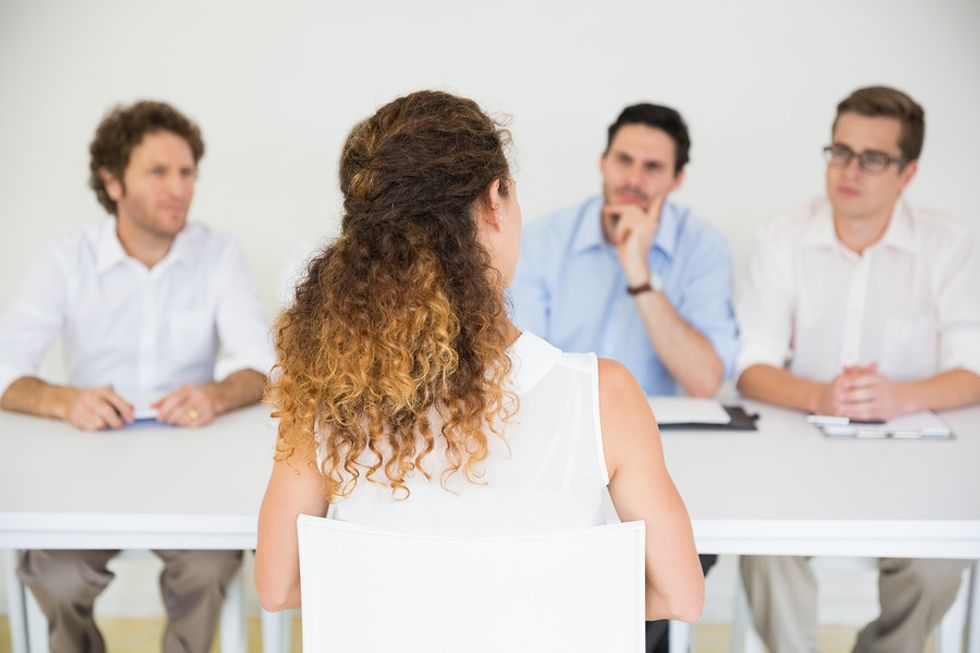 A job applicant answers a question from a panel of interviewers