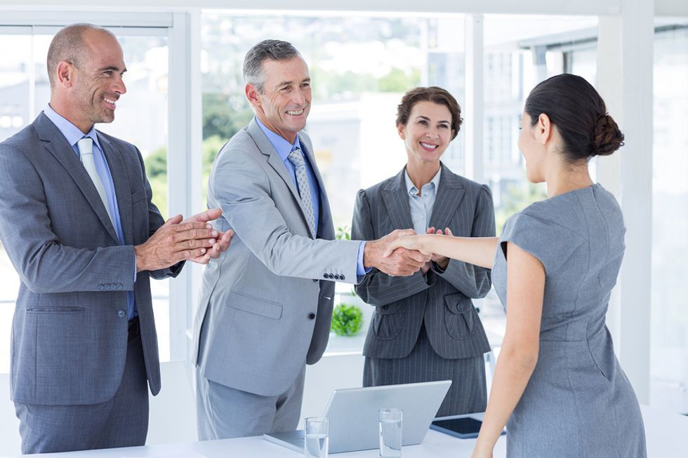 Professional woman thanks the panel of interviewers after her job interview