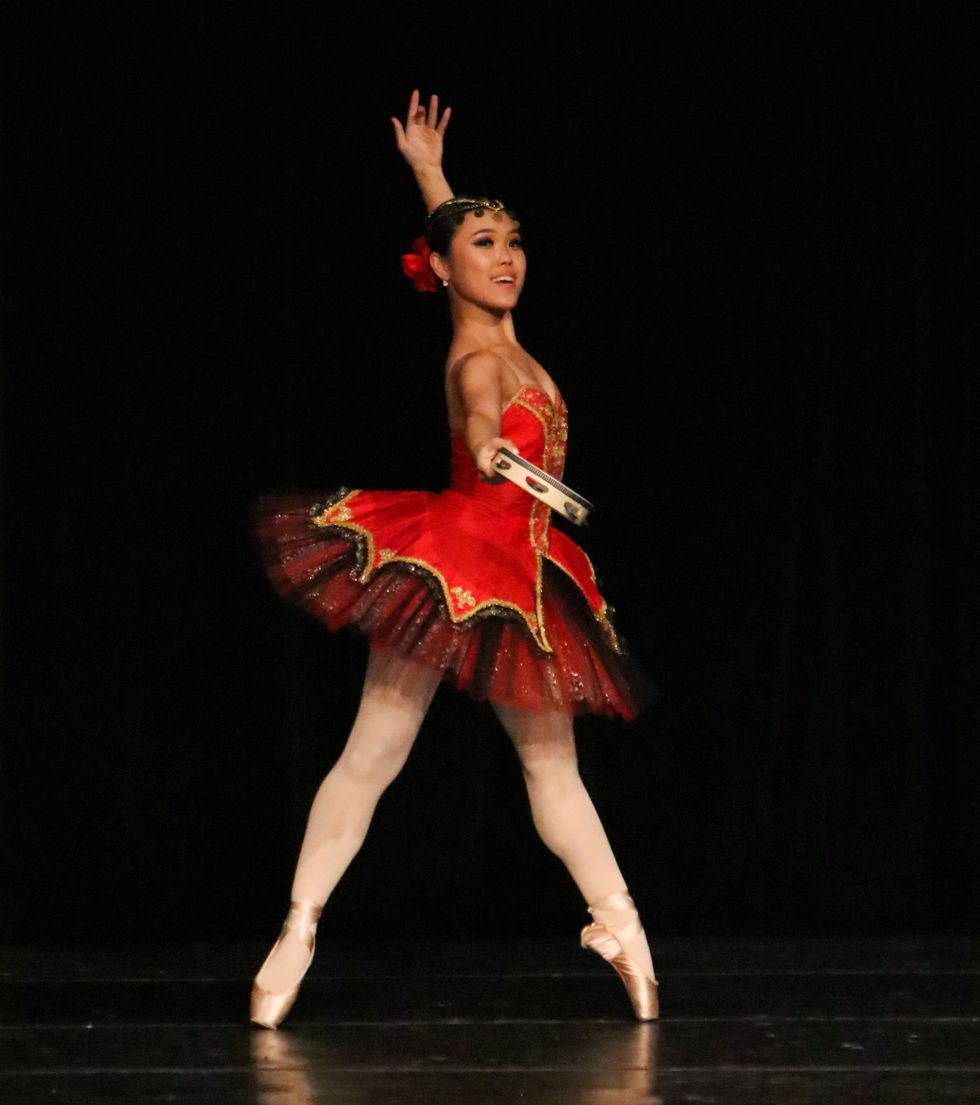 A young woman who seems to be performing the Kitri variation. She is in a slightly angled echappe on pointe, and wears a red and black tutu with a red hairpiece. She holds a tamborine which she extends out to the camera with one hand, the other arm behind her and up.
