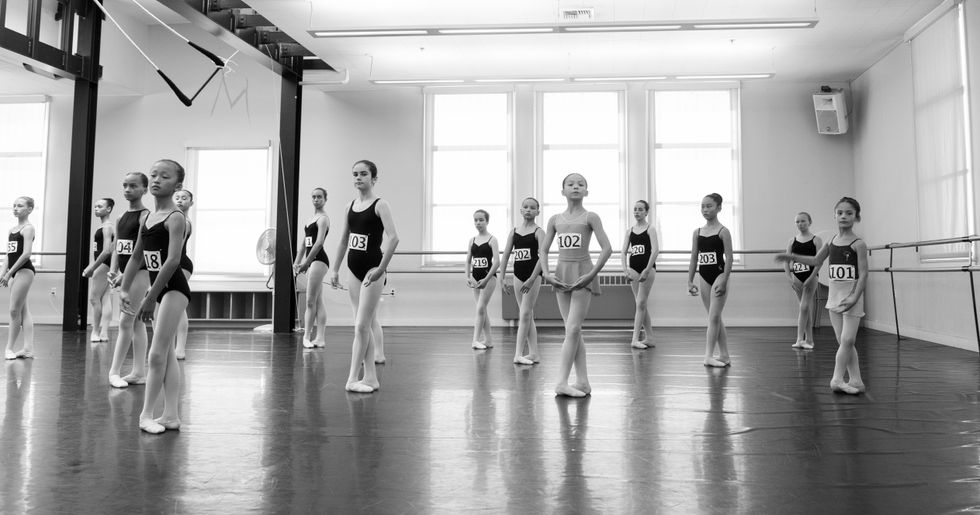 A master class of young girls. They each wear a number pinned to their leotard. They are in a large studio, standing in fifth position.