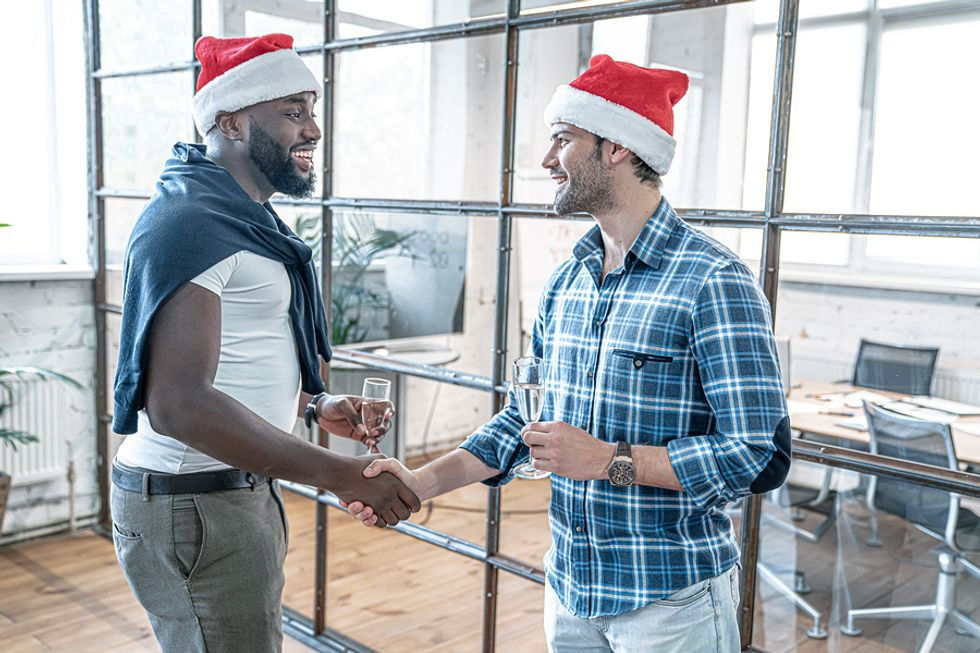 Two professionals network at a holiday office party
