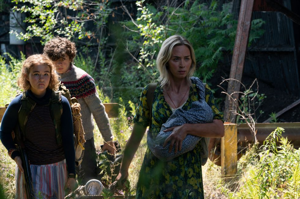 """Noah Jupe, Millicent Simmonds and Emily Blunt return as the Abbott family in """"A Quiet Place Part II."""" It's a tight angle shot of the actors walking through a sunny field surrounded by overgrown brush and grass. Blunt carries a baby in her left arm."""