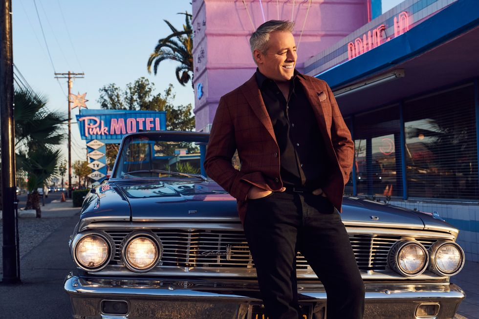 Actor Matt LeBlanc leaning against a classic Ford in front of a vintage diner.