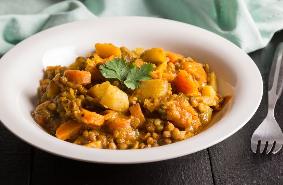 Lentil curry in a plate close up - Vegan recipe consisting of lentils, celery, carrot, potatoes and spices