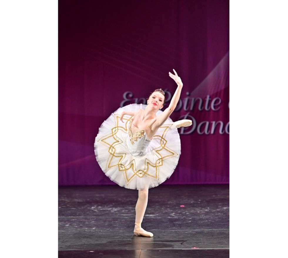Olivia Book, wearing a white tutu with gold trim, does a renvers\u00e9 in attitude with her right leg onstage during a ballet competition. She looks out to the audeince confidently, with her left arm stretched high above her and her right arm extended to the side.