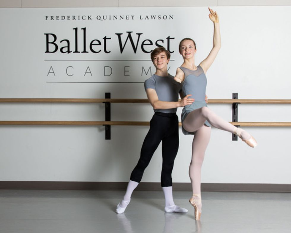 Olivia Book, waering a gray leotard and ballet skirt,  balances in attitude devant crois\u00e9 on pointe while her parnter Kesler Colton holds her waist, his right foot outstretched for balance. He wears a gray T-shirt, black tights, white socks and white ballet slippers.