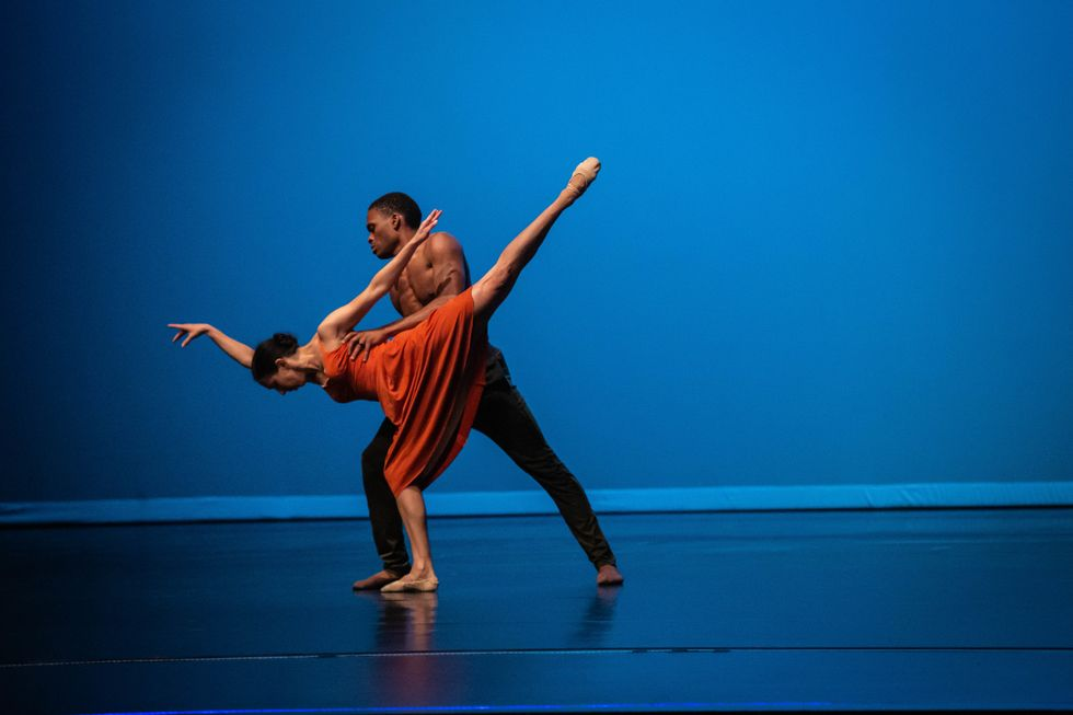 Hill is in a high arabesque pench\u00e9 with her face parallel to the floor. She wears an orange dress and ballet slippers, and is held under her armpits by Vessell, who is standing in a lunge and wearing black pants and no shirt.