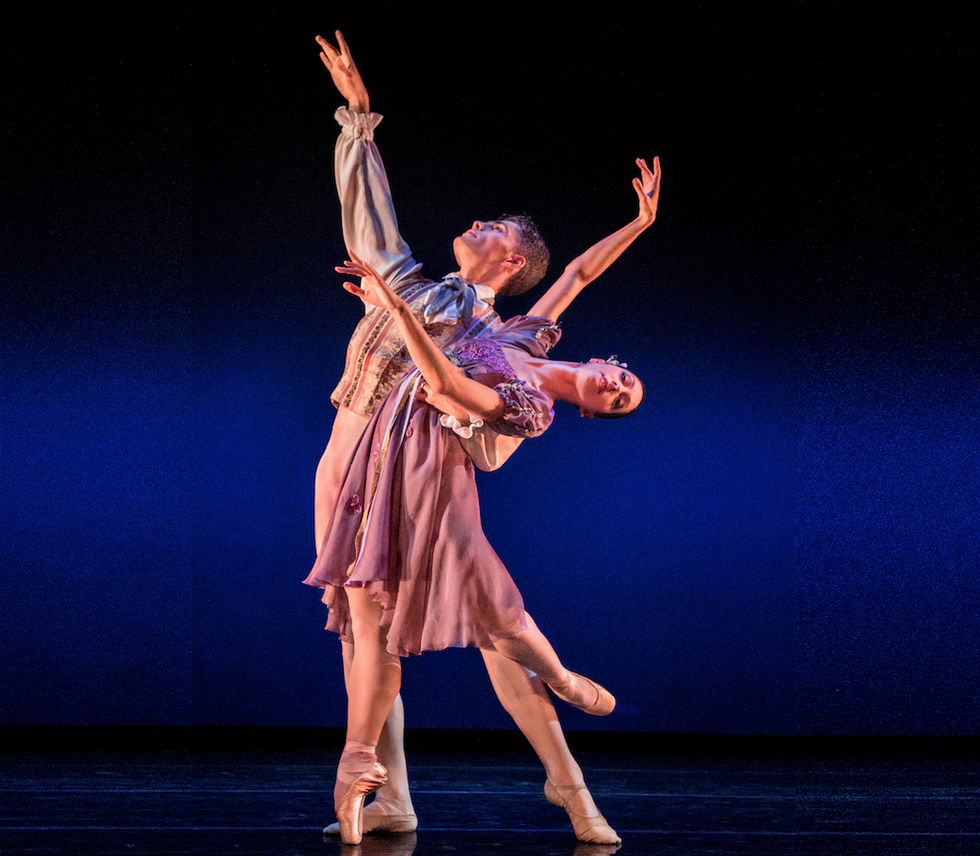Tilton, dressed in a white princely outfit and standing in a tendu with his arm in the air, holds Farris, who's balanced on pointe in a back attitude in a cambre back. She wears a purple floral dress.