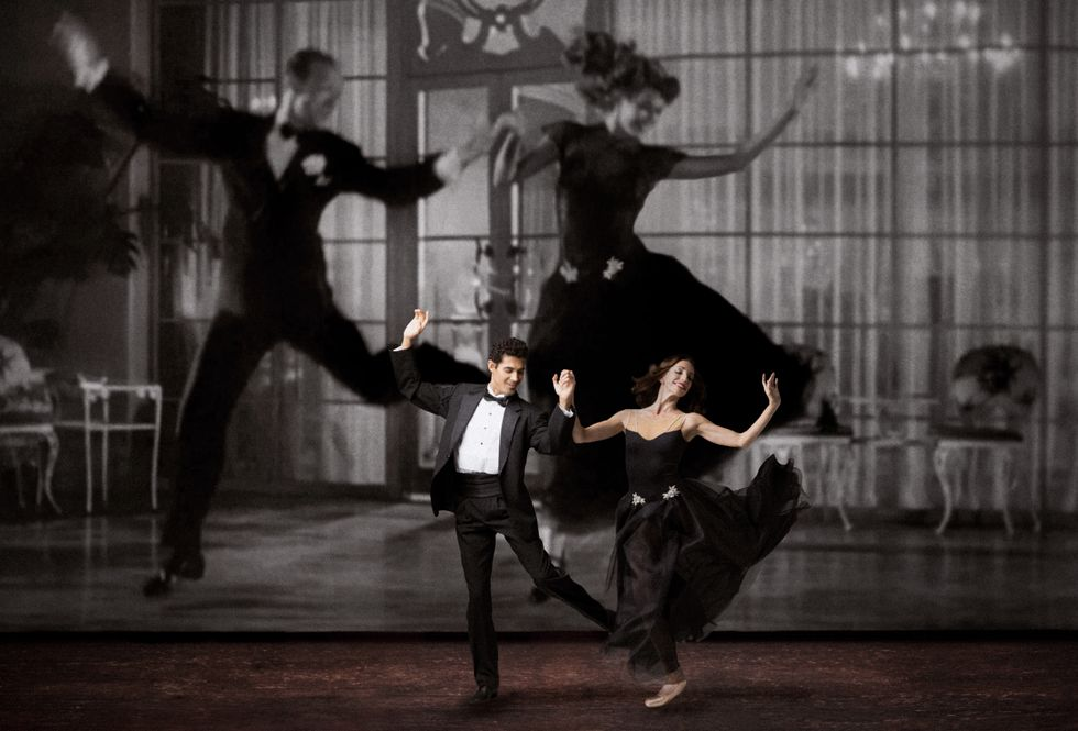 Renan Cerdeiro and Ashley Knox, holding hands, leap lightly onto their right feet, their arms thrown up and their left leg kicked up beside them. He wears a black tuxedo and she wears a strapless black gown. Behind them onstage looms a giant black-and-white projection of Fred Astaire and Rita Hayworth, wearing similar costumes.