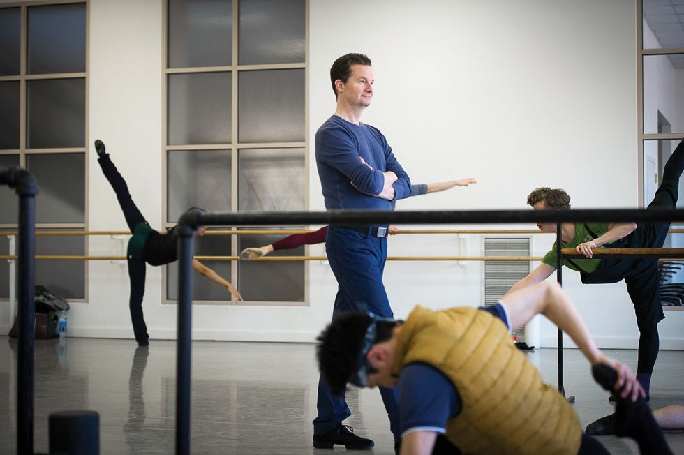Stark dressed all in blue with his arms crossed, walks through a ballet studio during a men's class. Dancers are stretching at the barre all around him.