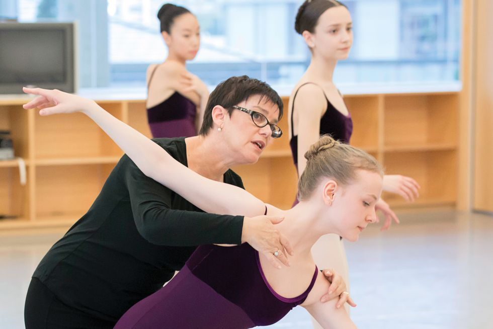 Hess, wearing all black, plastic framed glasses and pearl earrings, leans over Galway to demonstrate. Two other young ballet students stand behind her in a well-lit studio. All students wear purple velvet leotards and pink tights.