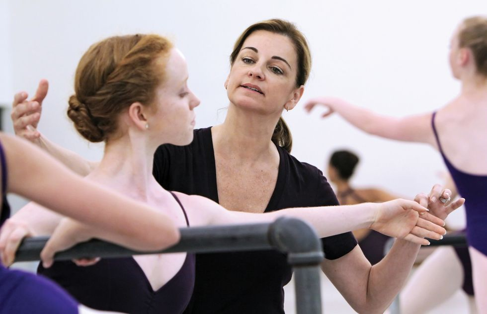 Power, wearing a black v-neck t-shirt and a ponytail, adjusts the arms of a young red-haired ballet student at the barre. They're surrounding by other students, all wearing purple leotards.