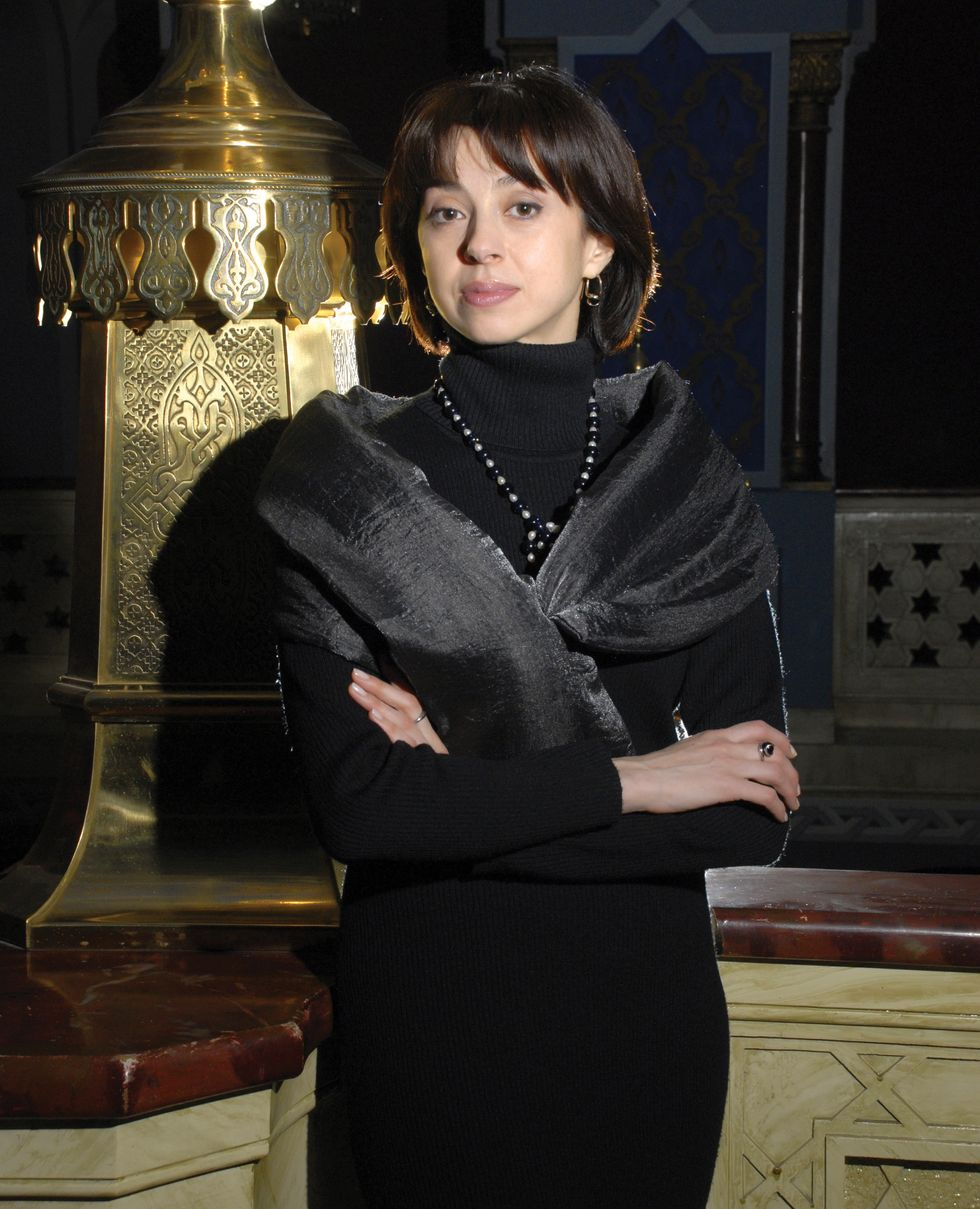 Ananashvili wearing a black dress, scarf and necklace stands in front of a glamorous Russian stage looking background with her arms crossed.