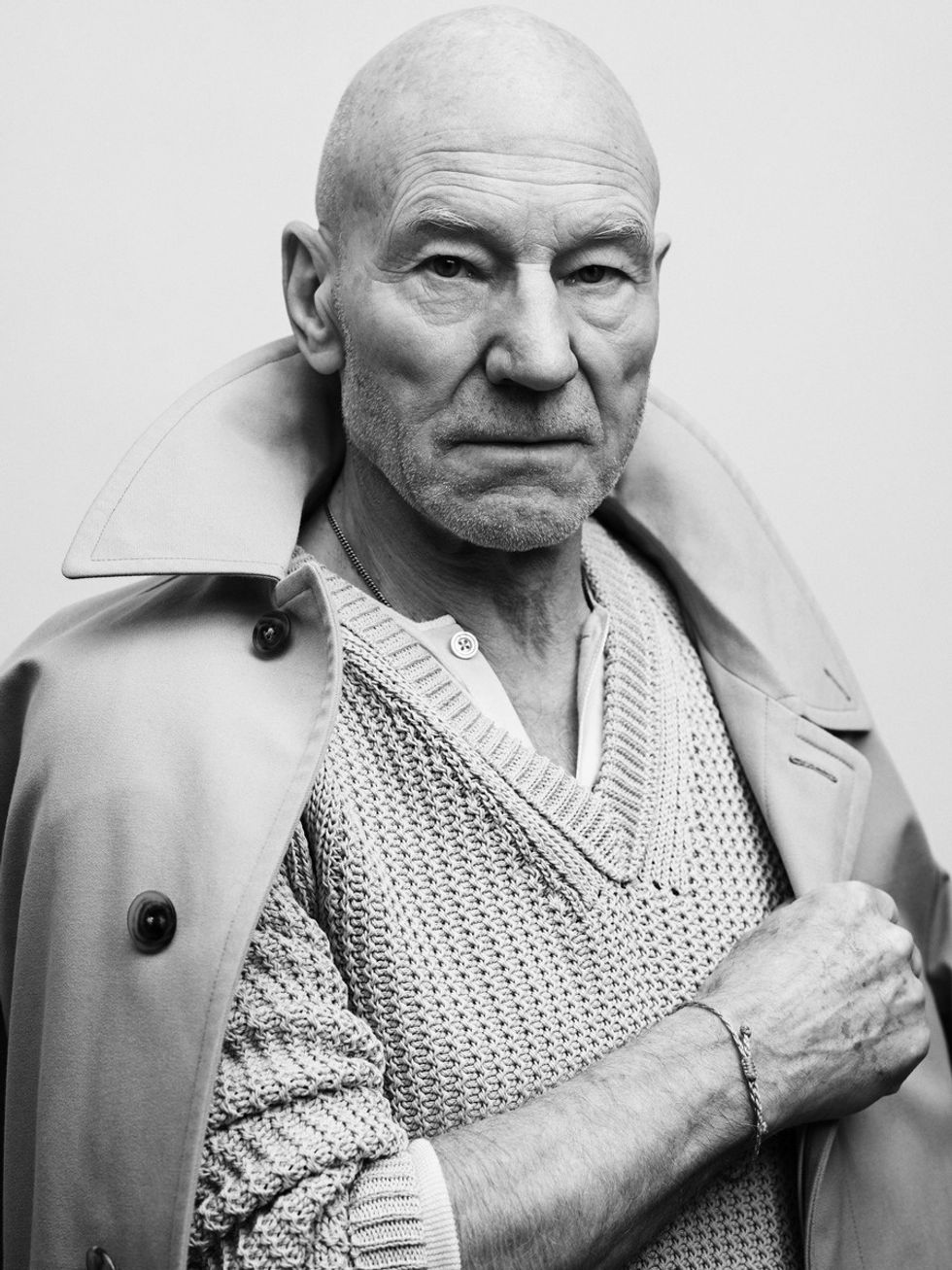 Black and white photo of Sir Patrick Stewart wearing a cable-knit sweater and trenchcoat.