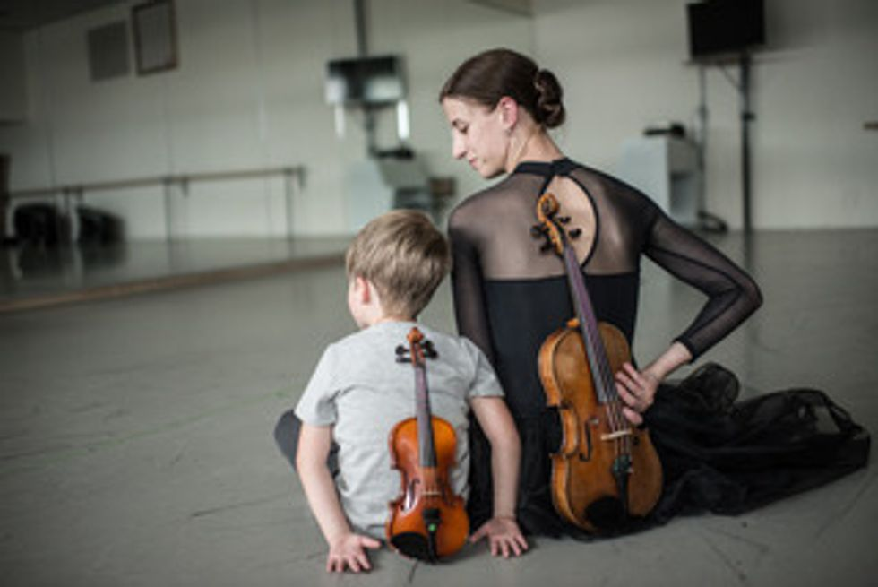 Maria Seletskaya sits in the studio with her son, each of them with a violin behind their backs