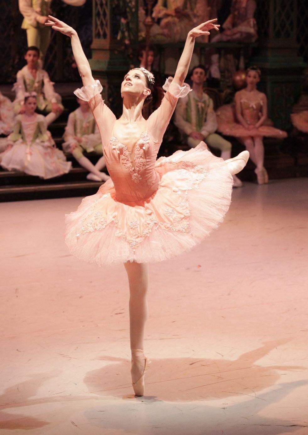 Maria Seletskaya wearing a pink tutu performing an arabesque balance on pointe