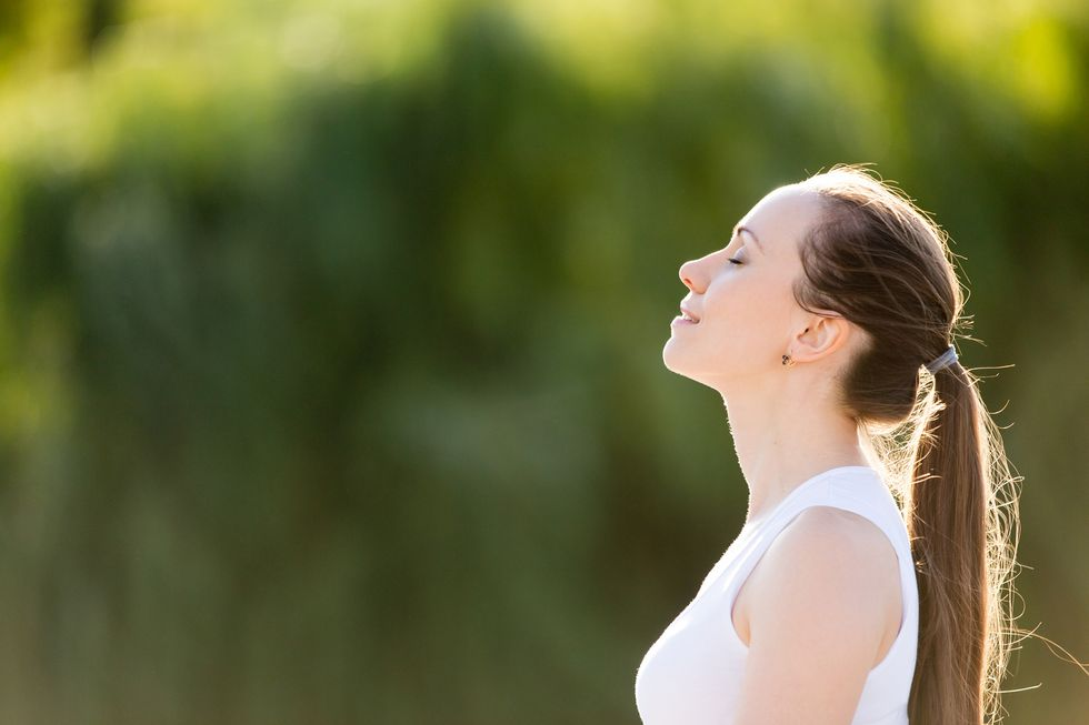 A woman sits outdoors and takes a deep breath