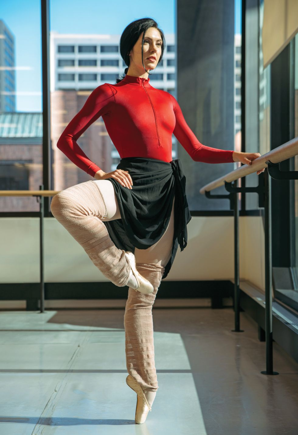 Sisk, dressed in a red leotard and black skirt and legwarmers, stands in a pass\u00e9 on pointe with one hand on the barre.