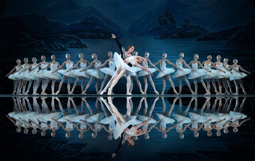 A background of ballerinas dressed as swans frame two dancers. The man, in white tights and a velvet jacket supports the ballerina, in a white swan tutu, who is collapsed over his arm.