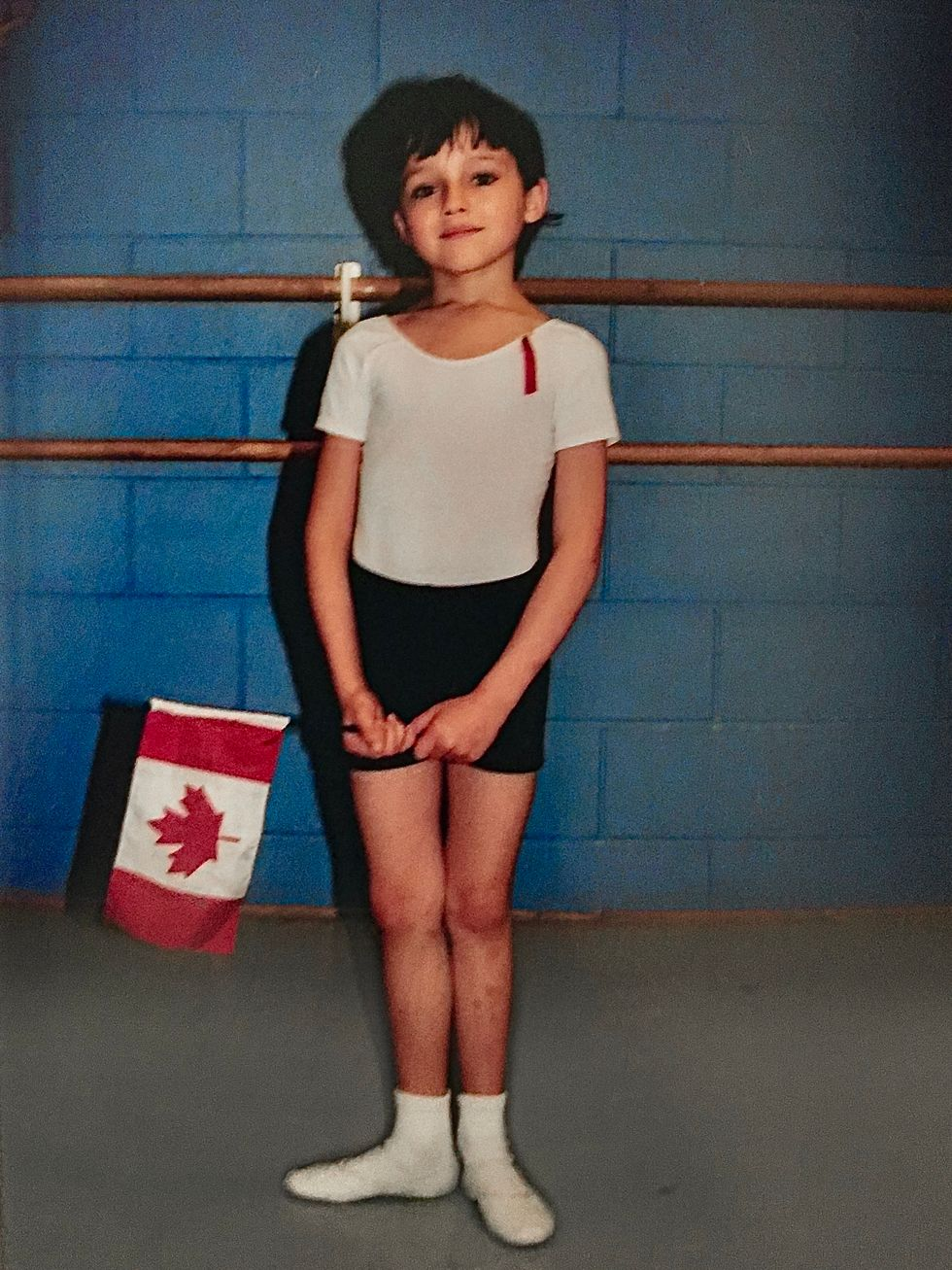 A very young Frenette stands in first position in front of a barre in black shorts, white tee and white shoes with socks. He looks serene and holds a small Canadian flag in his hands.