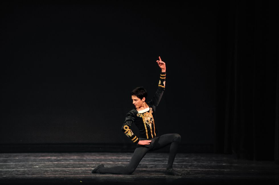 A young Frenette in black tights and a black and gold velvet jacket kneels onstage with one hand on the hip and the other in the air. He looks to the side, as if defiantly at the end of a variation.