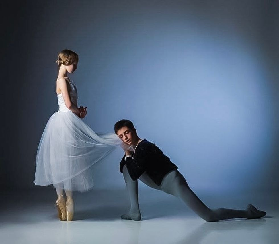 Frenette in a black jacket and grey tights kneels at Crymble's feet, holding the hem of her skirt against his cheek. She stands in a romantic tutu very upright on pointe with her hands held in the classic Giselle formation.