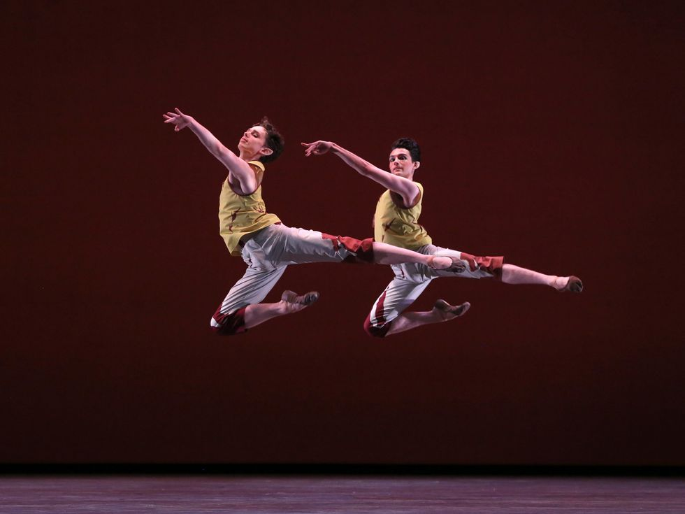 Frenette and Holloway, dressed in patterned grey and red capri pants and yellow and red tops stag leap through the air.