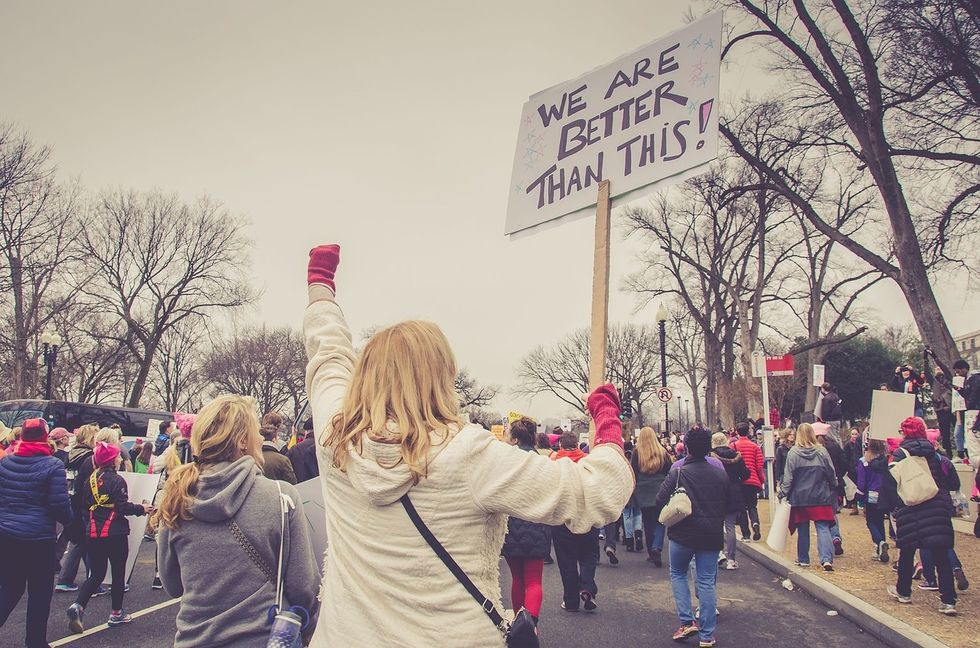 """Woman holding sign saying """"We are better than this!"""". Crowd marching"""