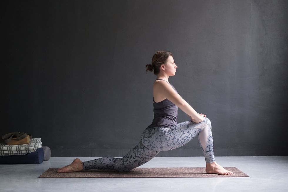 Woman in a low lunge stretching before work