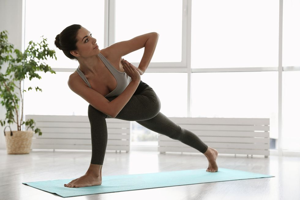 Woman in crescent lunge position stretching before work