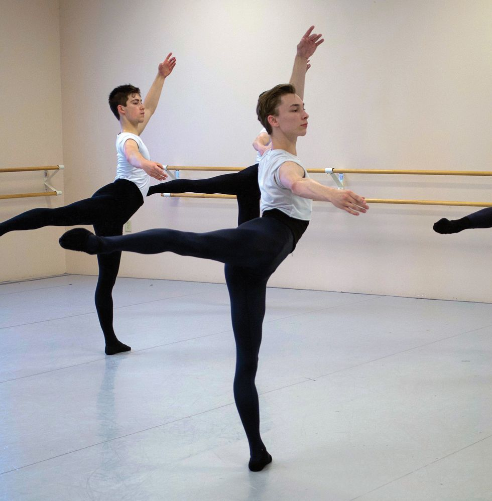 Three boys in black tights and white tee shirts stand in back attitude in a ballet studio.