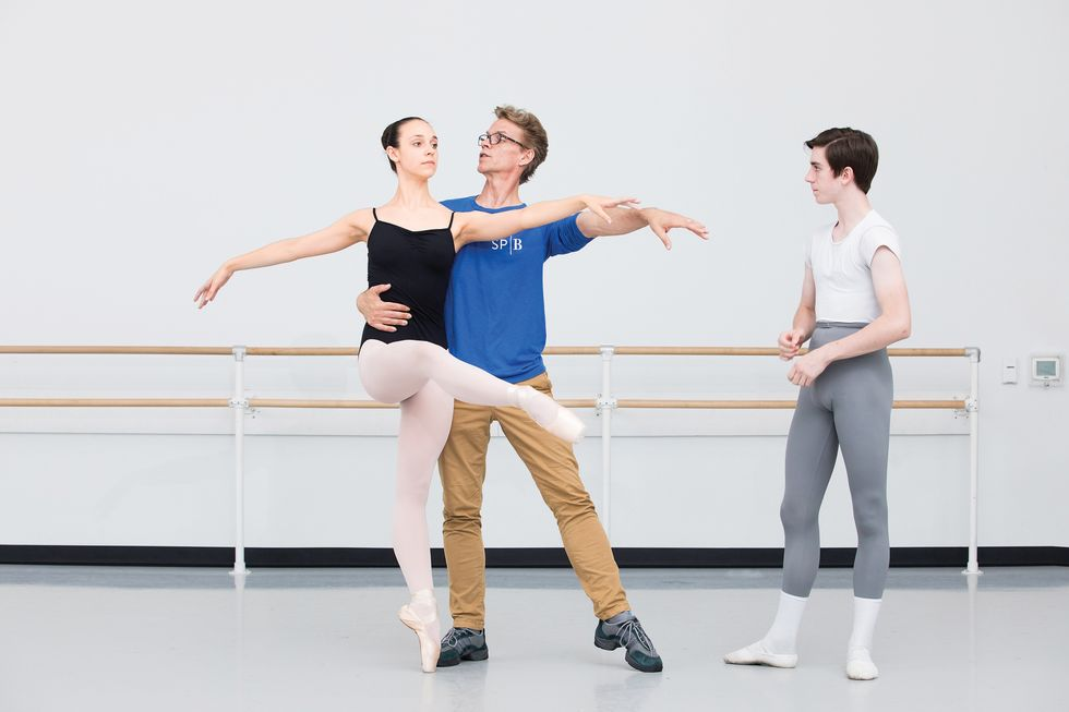 A young ballerina in pink tights and black leotard is being partnered by Payne, while he explains what he's doing. A male student in gray tights and a white tee stands to the side, waiting his turn.