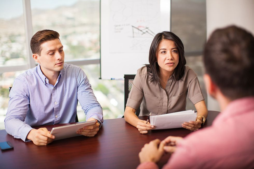 Interviewers ask an engineering job candidate a question