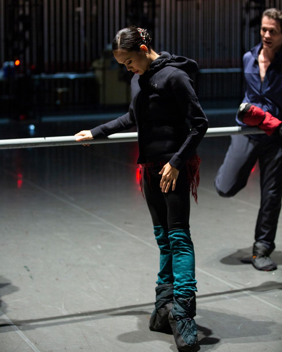 Pantastico, dressed in warm up clothes and booties, stands at the barre in first position relev\u00e9, looking down at her feet.